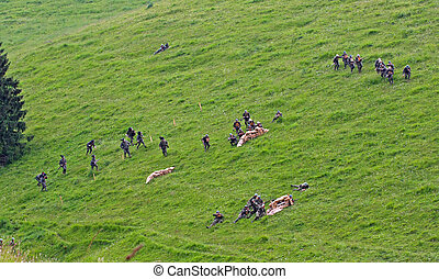 platoon of soldiers in uniform while crossing the line of enemy defense on the lawn in the mountains