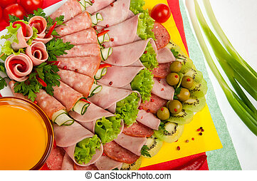 platter with cold meat decorated with lettuce - close-up of...