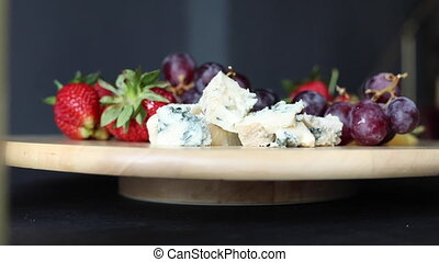 Stock footage of a wooden platter with fresh strawberries, cherries, cheese and grapes twisting in close-up.