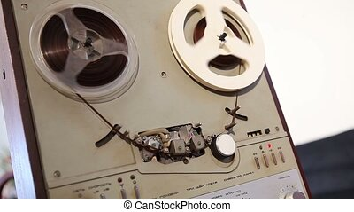 Play and rewind the tape in the old reel tape recorder, Old reel-to-reel tape deck, the tape is twisted in coils on record player
