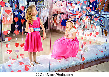 0ac6b80b35c Two cute little girls in beautiful dresses posing in the window of children s  clothing store. Kid s fashion. Seasonal sale and shopping.