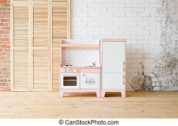 Play kitchen for children. Pink and white wooden toy kitchen with sink, oven and fridge in light room on white brick wall background