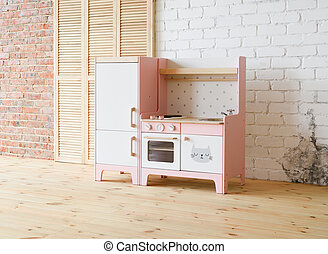 Play kitchen for children. Pink and white wooden toy kitchen with sink, oven and fridge in light room with wooden floor and white brick wall