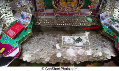 Play machine with many coins and dollars inside, closeup view