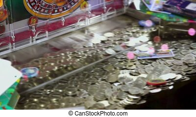 Play machine with many coins on moving tray inside, closeup view