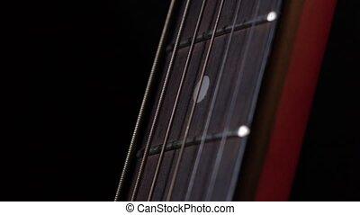 Play strings of acoustic guitar, down view, third string, on black, close up, slow motion