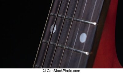 Play strings of acoustic guitar, side view, third string, on black, close up, slow motion