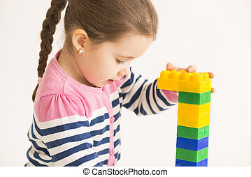Little girl playing with construction blocks, studio shot on white background
