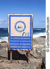 Warning sign at the black beach of janubio