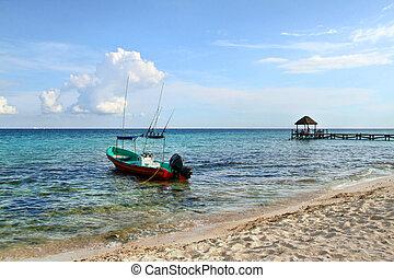 Hermosa playa en Playa del Carmen, Mexico con un barco listo para salir de pesca.