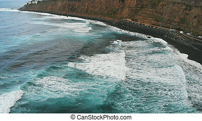 Playa del Socorro - a small cozy beach with black volcanic sand, and cinematic views of the Atlantic Ocean. Huge waves of turquoise color fall on the coast of the island of Tenerife, Spain