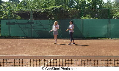 Player and her coach learning during a tennis class on the...