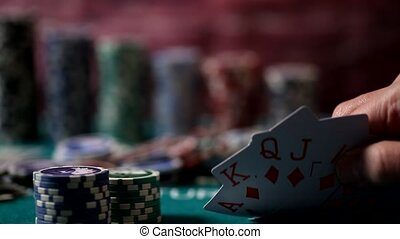 Player holding Royal Flush cards in hand. Chips, cards and dices on poker table in casino.