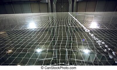 players play on Soccer field of stadium with light. view begins from ceiling through the net