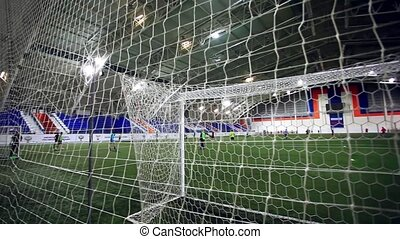 players play on Soccer field of stadium with light. view through the net