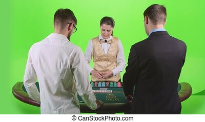 Players play poker in casino at the green table. Green...