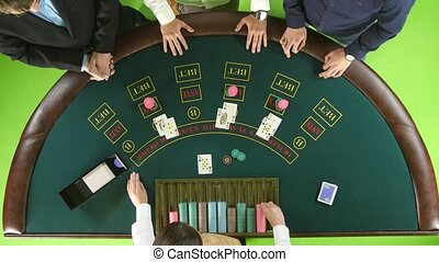 Players play poker in casino at the green table. Green screen. Top view
