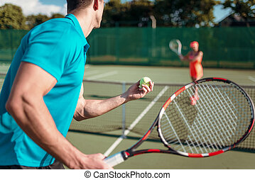 Players with rackets on outdoor tennis court