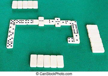 playfield of dominoes board game with white tiles on green ...