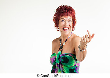 A red head are getting photographed dressed in a colourful, yet elegant dress.