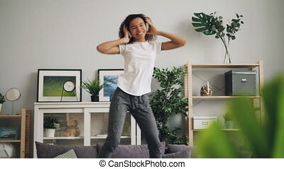 Playful African American woman is jumping dancing on couch...
