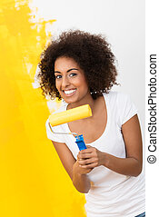 Playful African American woman painting