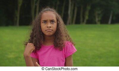 Playful african little girl plotting naughty trick - ...