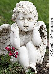 playful angelic figurine sitting in garden on flowerbed