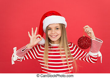 Playful baby. Christmas party. Winter holidays. Playful mood. Christmas celebration ideas. Shine and glitter. Child Santa Claus costume hat. Happy smiling face. Beautiful detail. Positivity concept