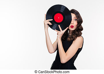 Playful beautiful woman covered half of face with vinyl disc