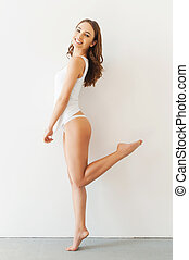 Playful beauty. Full length of attractive young woman in white tank top and panties posing while standing against white background