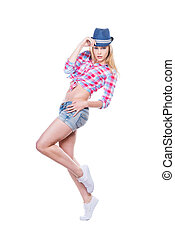 Playful beauty in style. Full length of beautiful young woman in funky wear adjusting her hat and looking at camera while standing against white background