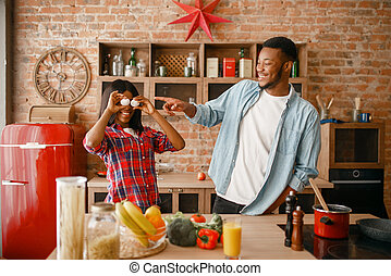 Playful black couple cooking dinner on the kitchen