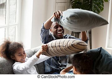 Playful black family playing with pillows at home