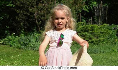 Playful blond girl throw away hat. Happy girl with pink...