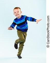 Playful little boy on studio, light blue background