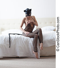 Playful catwoman posing in hotel room