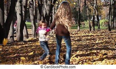 Playful children - Two little girls spinning in autumn park...