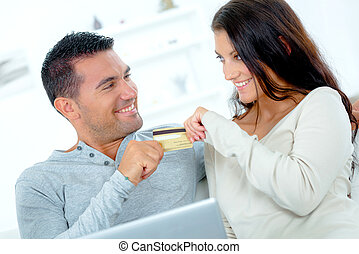 Playful couple fighting over a credit card