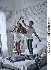 Playful couple. Full length of beautiful young couple...