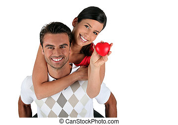 Playful couple holding heart-shaped object