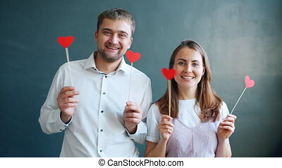 Playful couple holding hearts moving hands smiling feeling ...