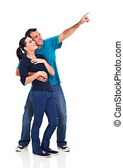 playful couple pointing away - happy playful couple pointing...