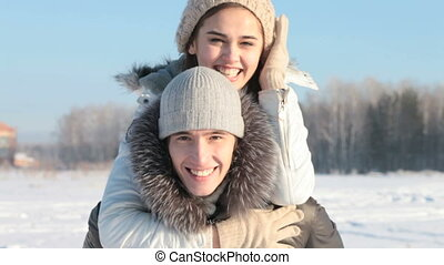 Playful couple - Boy holding girlfriend piggyback, both...