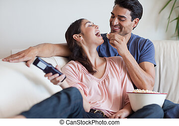 Playful couple watching TV while eating popcorn in their ...