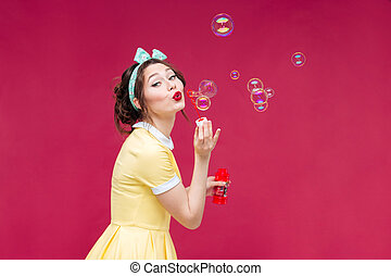 Playful cute pinup girl in yellow dress blowing soap bubbles