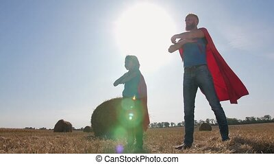 Playful dad and son dressed as supermen outdoor