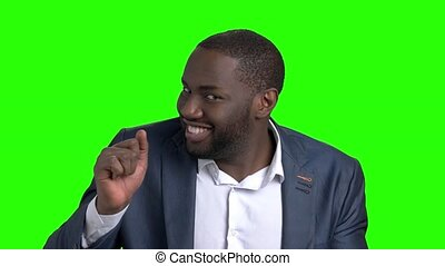 Playful dark-skinned businessman on green screen. Young...