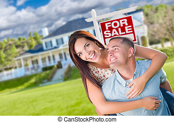 Playful Excited Military Couple In Front of Home with For Sale Real Estate Sign.