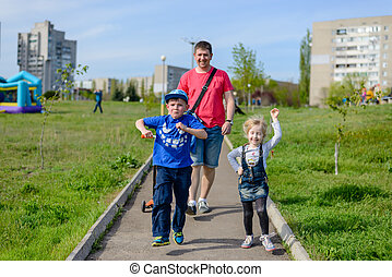 Playful exuberant young children with their father